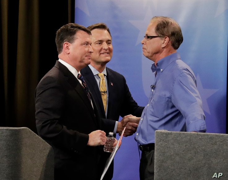 Senate candidates from left, Todd Rokita, Luke Messer and Mike Braun speak with each other following the Indiana Republican senate primary debate in Indianapolis, April 30, 2018.