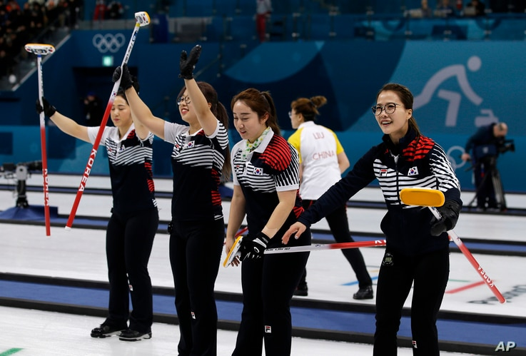 South Korea's women's curling team celebrate after beating Russian athletes during their match at the 2018 Winter Olympics in Gangneung, South Korea, Feb. 21, 2018.