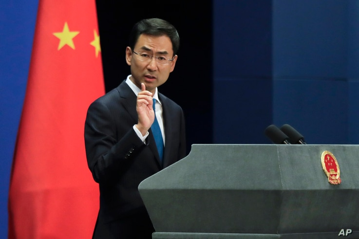 FILE - Chinese Foreign Ministry spokesman Geng Shuang gestures as he speaks during a daily briefing at the Ministry of Foreign Affairs office in Beijing, Sept. 4, 2017.