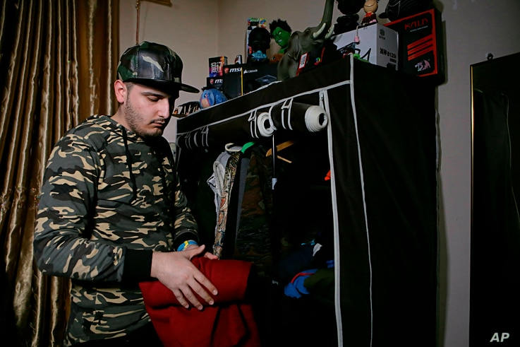 Rapper Ahmed Chayeb, better known as Mr. Guti, chooses his outfit for his next performance, at his home in the southern port city of Bqasra, Iraq,  Feb. 12, 2019. Chayeb raps about anger and disillusionment in his hometown of Basra, which saw riots ...