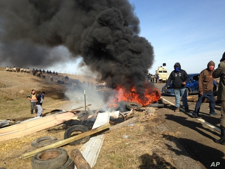 Dakota Access oil pipeline protesters burn debris as officers close in to force them from a camp on private land in the path of pipeline construction, Oct. 27, 2016 near Cannon Ball, N.D.