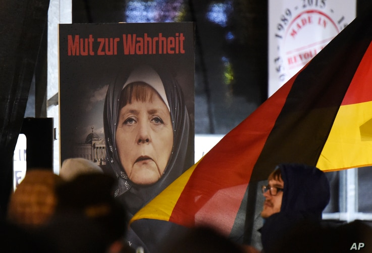 "FILE -A poster with the writing ""Courage to speak the truth"" depicts German Chancellor Angela Merkel wearing a veil  during a demonstration of the Legida anti-Islamization movement, an offshoot of Pegida, in Leipzig, Jan. 30, 2015."
