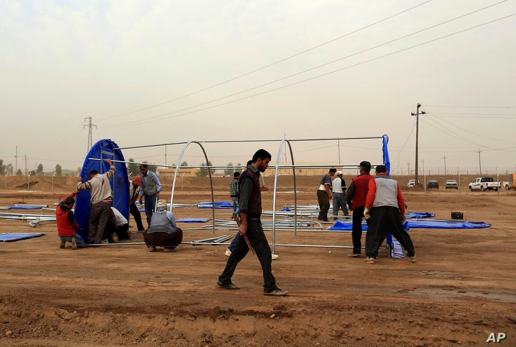 FILE - Workers set up a camp for displaced Iraqis in Khazer, Iraq, Oct. 19, 2016. More than 25,000 troops have mobilized for the fight to free Mosul, Iraq's second largest city and the largest urban area controlled by the Islamic State militants.