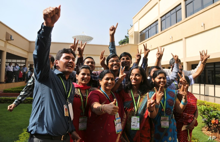 FILE - Indian Space Research Organisation scientists and officials pose for photos as they celebrate the success of Mars Orbiter Mission at their Telemetry, Tracking and Command Network complex in Bangalore, India, Sept. 24, 2014.