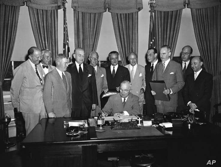 FILE - President Harry S. Truman signs a proclamation declaring into effect the 12-nation Atlantic Pact binding North America and Western Europe in a common defense alliance, Aug, 24, 1949. Witnessing the signing (L-R): Hoyar Miller of the United Kin...