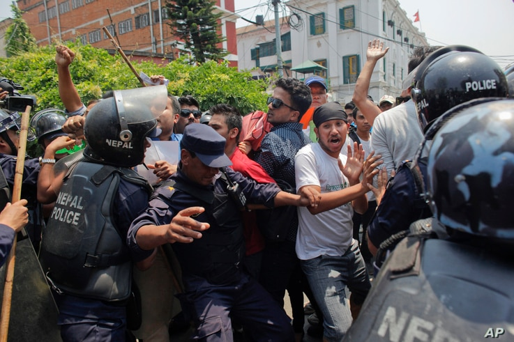 Nepalese protestors shout slogans against the government as they are stopped by police on the first anniversary of the devastating earthquake in Kathmandu, Nepal, April 24, 2016.