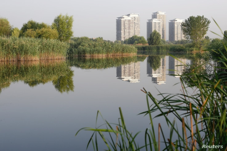 Blocks of flats are reflected in one of the lakes inside Vacaresti wetlands, in Bucharest, Romania, July 29, 2016.