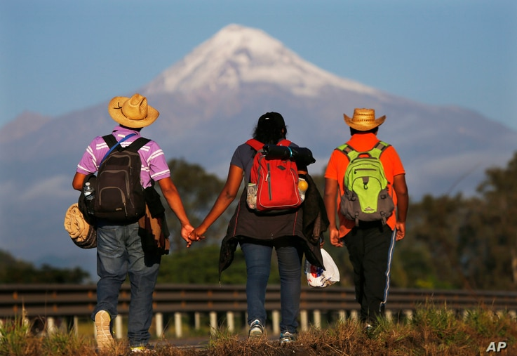 Central American migrants begin their morning trek facing Pico de Orizaba volcano as part of a thousands-strong caravan hoping to reach the U.S. border, upon departure from Cordoba, Veracruz state, Mexico, Monday, Nov. 5, 2018.