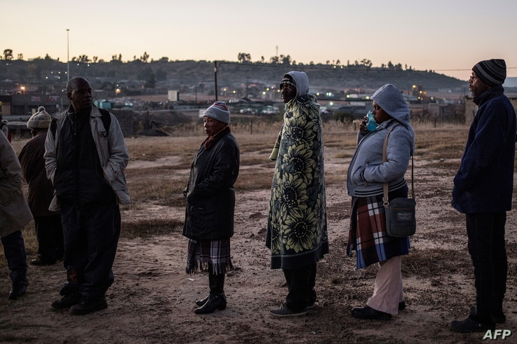 Voters queue outside a polling station in order to cast their ballot during the Lesotho's general elections on June 3, 2017 in Maseru.