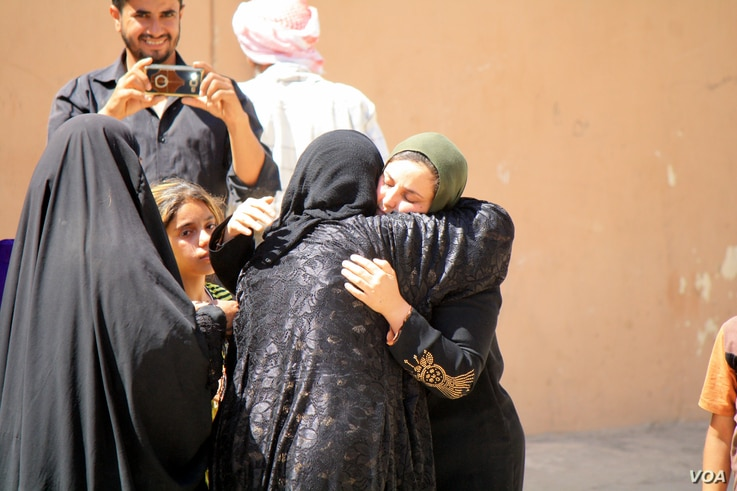 A family member takes pictures as a mother and daughter are reunited after nearly three years of separation in the days after Iraqi forces recaptured their family's neighborhood in Mosul, Iraq, June 1, 2017. (H.Murdock/VOA)