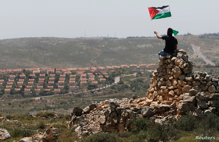 A protester waves a Palestinian flag in front of the Jewish settlement of Ofra during clashes near the West Bank village of Deir Jarir near Ramalla,h Apr. 26, 2013.