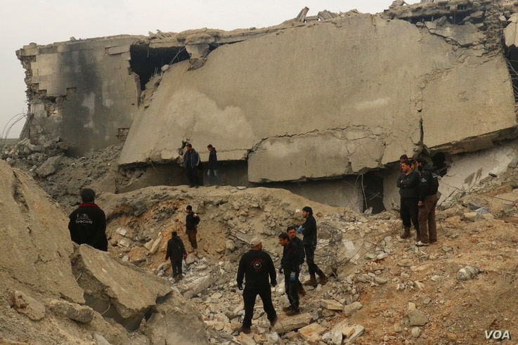 Civil defense members and other people inspect a damaged mosque after an airstrike on the village of al-Jinah, Aleppo province, in northwest Syria, March 17, 2017.
