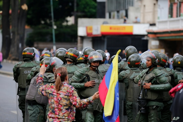 A woman holding a Venezuelan national flag heckles Bolivarian National Guardsmen blocking the passage of opposition members during a protest march against President Nicolas Maduro in Caracas, Venezuela, Jan. 23, 2019.