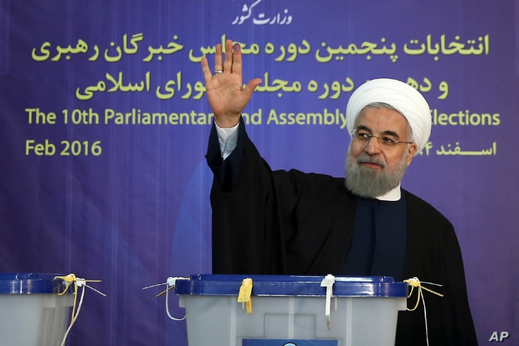 In this photo released by official website of the office of the Iranian Presidency, President Hassan Rouhani waves to media after casting his vote for parliamentary and Experts Assembly elections in Tehran, Iran Friday, Feb. 26, 2016.