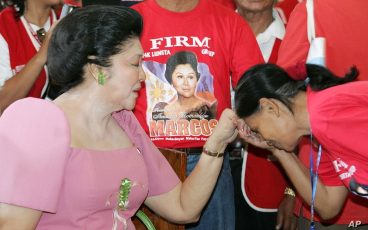 FILE - Imelda Marcos, left, is greeted by a supporter during the commemoration of the 89th birthday of her late husband, former strongman Ferdinand, in Batac, Ilocos Norte, northern Philippines on Monday, Sept. 11, 2006.