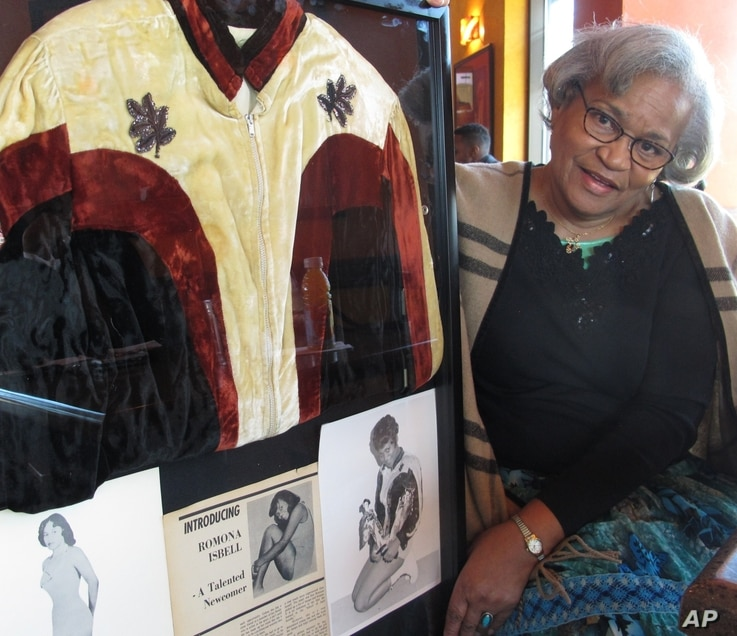 Ramona Isbell talks about her days as a professional wrestler in the 1960s and 1970s, beside a framed collage of mementos including publicity photos and a jacket, in Columbus, Ohio, March 19, 2018.