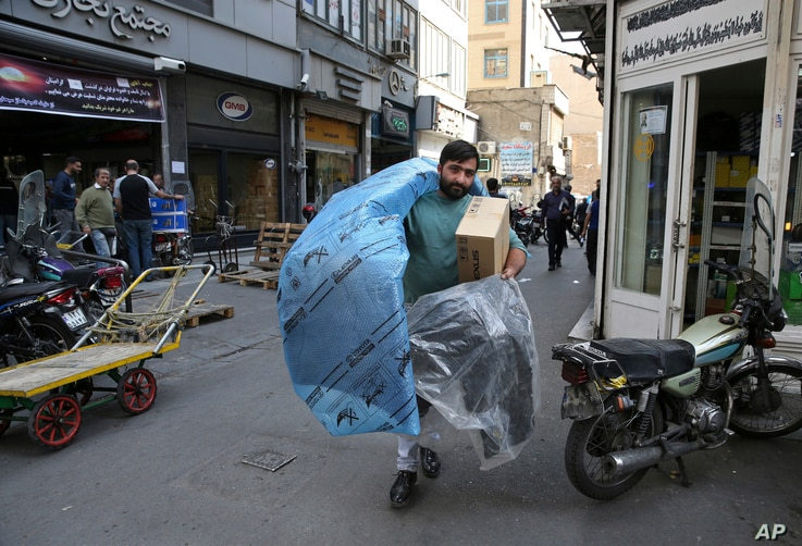 FILE - A man carries car parts at a market in downtown Tehran, Iran, Oct. 9, 2017. Iranians hope lifting of most international sanctions under Tehran's landmark 2015 nuclear deal with the West would revive their country's long-suffering economy.
