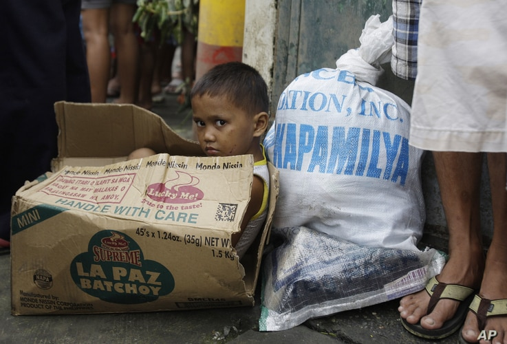 A Filipino boy sits inside an empty carton of noodles as he waits for his parents to receive relief goods at a hardly hit residential area in suburban Quezon City, north of Manila, Philippines, August 13, 2012.