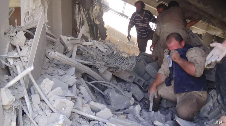 This image taken Sept. 30, 2015 posted on the Twitter account of Syria Civil Defence, also known as the White Helmets, a volunteer search and rescue group, shows the aftermath of an airstrike in Talbiseh, Syria.