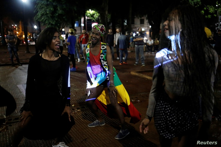 Gaby (left), 18, Vitor (center), 21, and Pamela, who are among members of lesbian, gay, bisexual and transgender (LGBT) community, dance during an event of Arouchianos collective project at Arouche Square in downtown Sao Paulo, Brazil, Nov. 6, 2016.