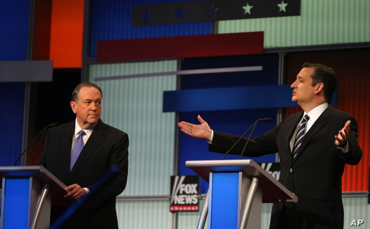 Sen. Ted Cruz, R-Texas, speaks as former Arkansas Gov. Mike Huckabee, left, listens during the first Republican presidential debate, Cleveland, IN, Aug. 6, 2015, in Cleveland.