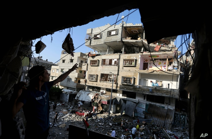 Palestinians inspect the rubble of a house after it was hit by an Israeli missile strike in Gaza City, July 10, 2014.