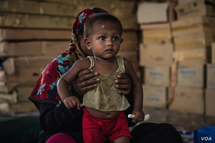 A Rohingya refugee mother holds her recovering baby who has received treatment for malnutrition at an Action Against Hunger clinic in Ukhiya, Bangladesh, April 18, 2018. One-fifth of the children in the camps are malnourished, with 12 percent sufferi...
