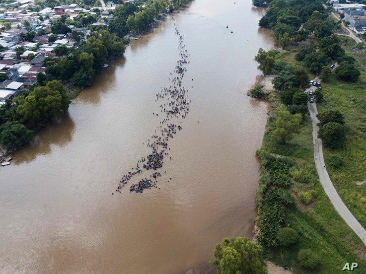 A new group of Central American migrants bound for the U.S border wade in mass across the Suchiate River, that connects Guatemala and Mexico, in Tecun Uman, Guatemala, Oct. 29, 2018.