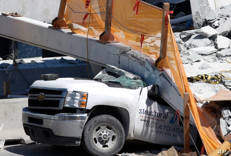 A crushed pickup truck is shown under a new pedestrian bridge, Friday, March 16, 2018, after it collapsed Thursday onto a highway at a Miami-area college.