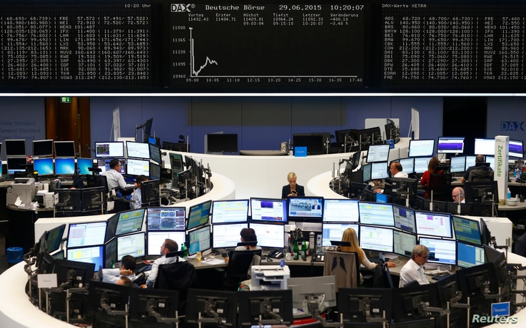 Traders sit at their desks in front of the DAX board at the Frankfurt stock exchange, Germany, June 29, 2015.