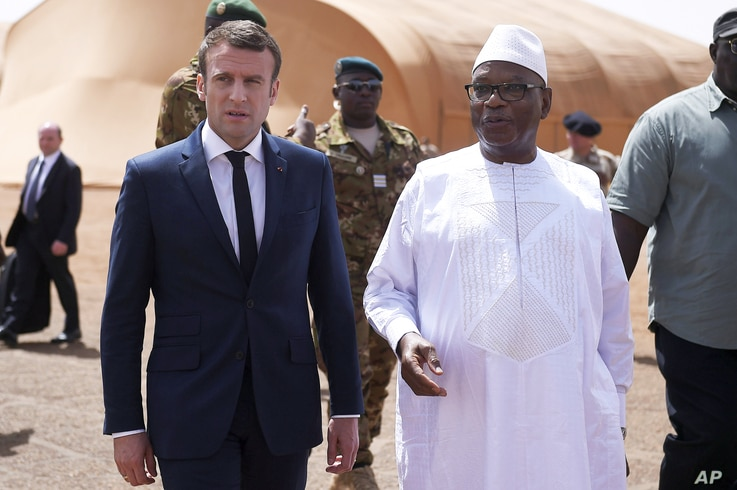 French President Emmanuel Macron, left, talks to Mali's President Ibrahim Boubacar Keita as they meet French soldiers of Operation Barkhane, France's largest overseas military operation, in Northern Mali, May 19, 2017.