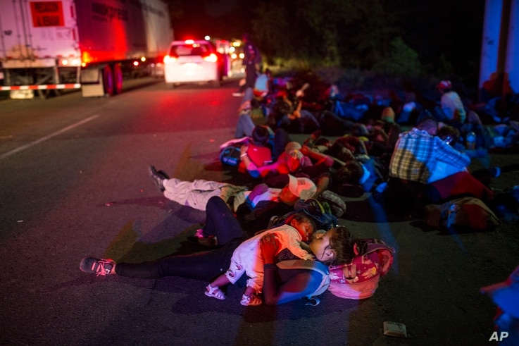 Early in the morning migrants sleep next to the highway waiting for a ride, as a thousands-strong caravan of Central American migrants slowly makes its way toward the U.S. border, between Pijijiapan and Arriaga, Mexico, Oct. 26, 2018.