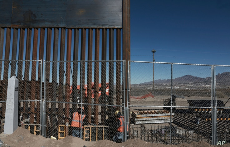 Work continues on a taller fence in the Mexico-US border area separating the towns of Anapra, Mexico and Sunland Park, New Mexico, Jan. 25, 2017.