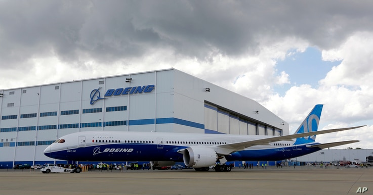 FILE - Boeing employees stand near the new Boeing 787-10 Dreamliner at the company's facility in South Carolina after conducting its first test flight at Charleston International Airport in North Charleston, S.C., March 31, 2017.