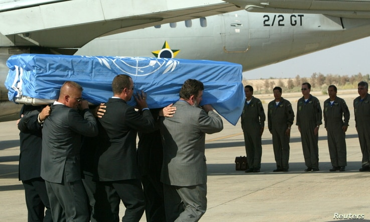 FILE - The crew of a Brazilian military plane stands at attention as the coffin with the body of the U.N. special envoy to Iraq, Sergio Vieira de Mello is put on the plane at the airport in Baghdad, Aug.  22, 2003.