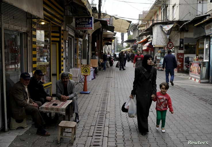 A Syrian woman and her child walk along a street in the neighborhood of Basmane, which is filled with transient migrants on their way to Europe, in the Aegean port city of Izmir, western Turkey, March 8, 2016.