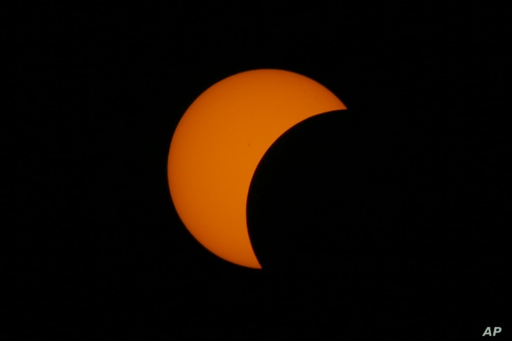 FILE - A partial solar eclipse occurs March 9, 2016, as seen from Taguig city, east of Manila, Philippines.