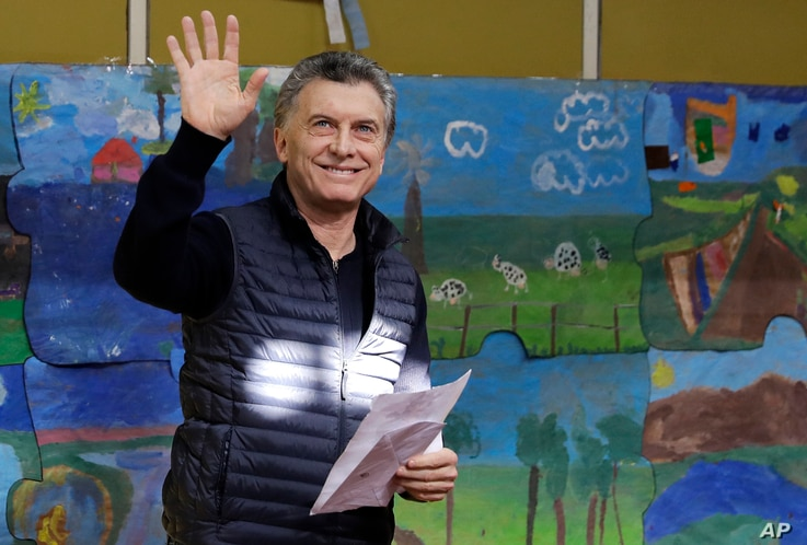 Argentina's President Mauricio Macri waves to followers before voting during the open primary legislative elections in Buenos Aires, Argentina, Aug. 13, 2017.