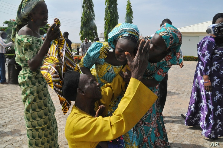 FILE - Family members celebrate as they embrace a relative, one of the released kidnapped schoolgirls, in Abuja, Nigeria, May 20, 2017. The 82 Nigerian schoolgirls recently released after more than three years in Boko Haram captivity reunited with...