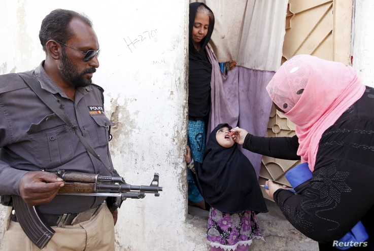 A girl receives polio vaccine drops at the door step of her family home in Karachi, Pakistan, February 15, 2016.
