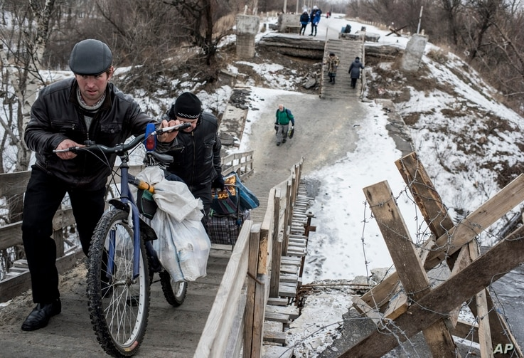 Local residents walk across a bridge damaged during fighting between Ukrainian government forces and Russia-backed rebels in Stanytsia Luhanska, Luhansk region, eastern Ukraine, Jan. 16, 2016.