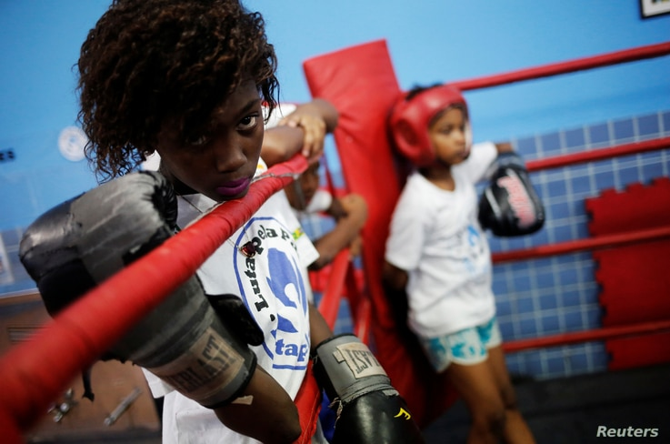 A girl looks at other children practicing on a boxing ring during an exercise session at a boxing school, in the Mare favela of Rio de Janeiro, Brazil, June 2, 2016.