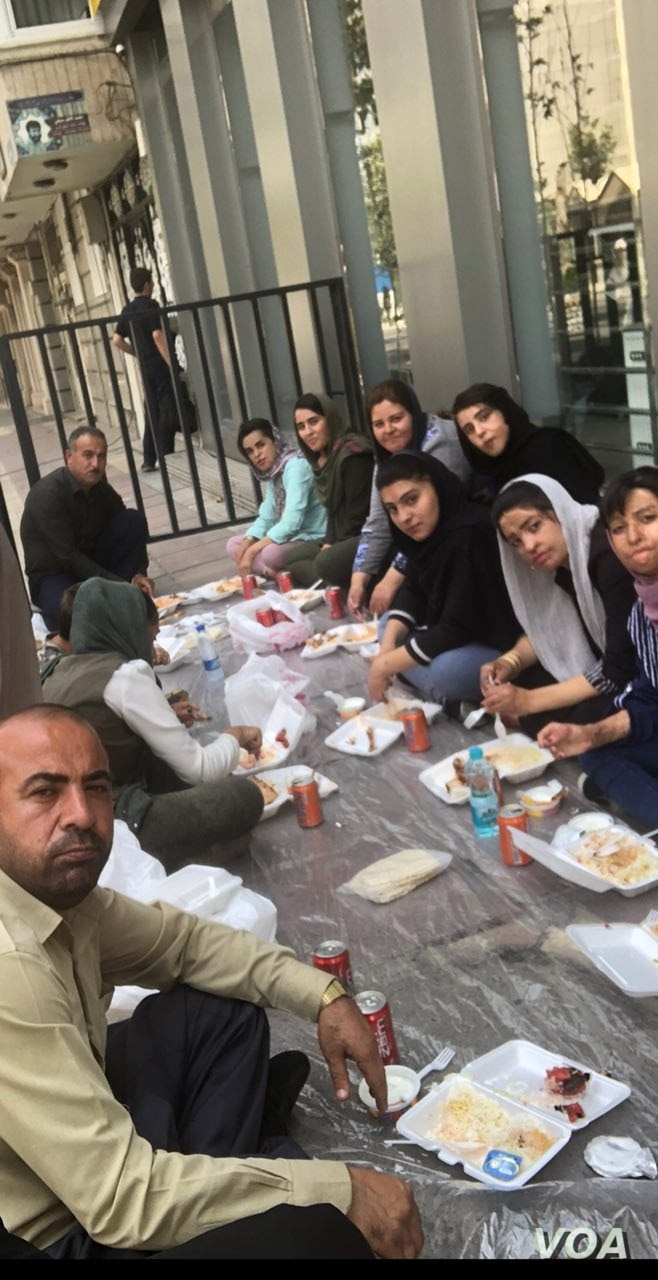 Shinabad school fire survivors and their supporters eat on a sidewalk near the Tehran office of President Hassan Rouhani, July 18, 2018.