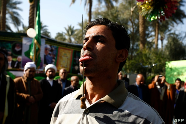 FILE - An Iraqi Muslim has a spike pierced into his tongue during a Sufi ritual in the Iraqi city of Hilla, south of Baghdad, Jan. 15, 2016.