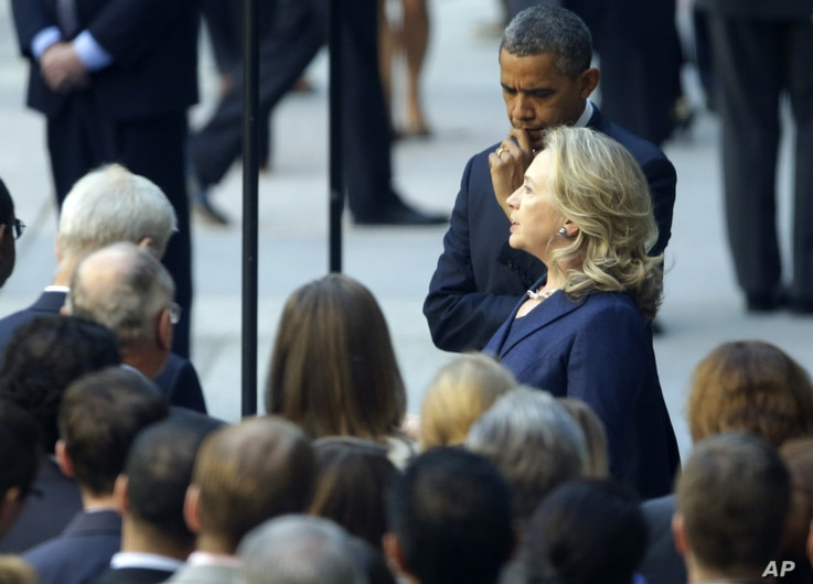 President Barack Obama listens as Secretary of State Hillary Rodham Clinton speaks with State Department personnel in the courtyard of the State Department in Washington, Sept. 12, 2012, after speaking at the White House concerning the recent deaths