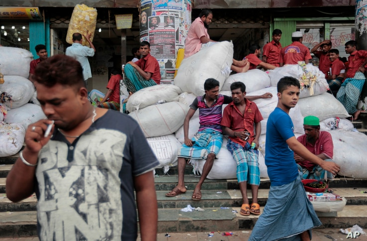 FILE - Bangladeshi laborers wait for work at a market area in Dhaka, Bangladesh, Aug. 13, 2016. But some in the low-lying delta nation are worried that the staggering influx of Rohingyas, if allowed to stay, could push the country's resources and e...