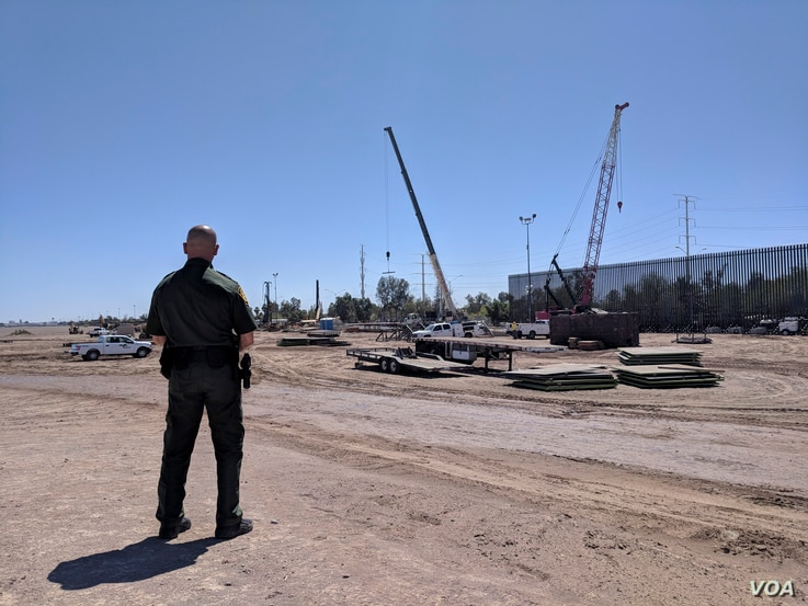 Border Patrol Sector Supervisor Jorge Rivera watches as construction workers build a portion of nine-meter-tall replacement fencing in Calexico, California.