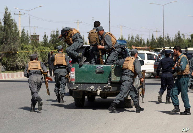 FILE - Afghan security personnel arrive at the site of a deadly attack on the Interior Ministry, in Kabul, Afghanistan, May 30, 2018.