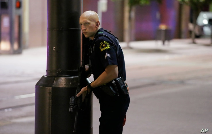 A Dallas policeman keeps watch on a street in downtown Dallas, Thursday, July 7, 2016.
