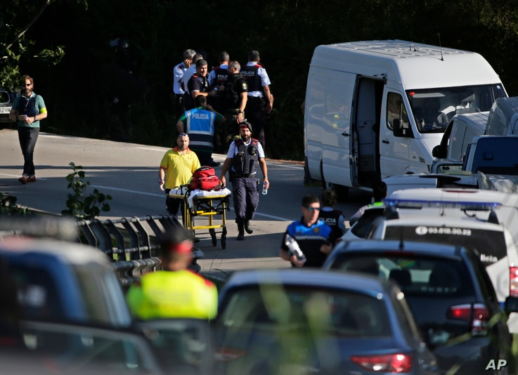 An ambulance stretcher is pushed on the road where Police bomb squad members work by a road near Subirats, Spain, Aug. 21, 2017.